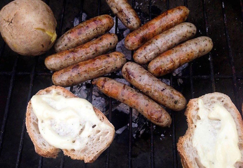 Auf einem Grill liegen Würstchen, Brot und Kartoffeln